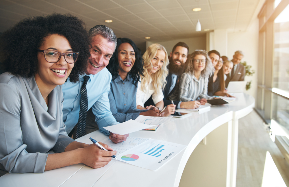 Group of smiling employees leaning against curved conference table